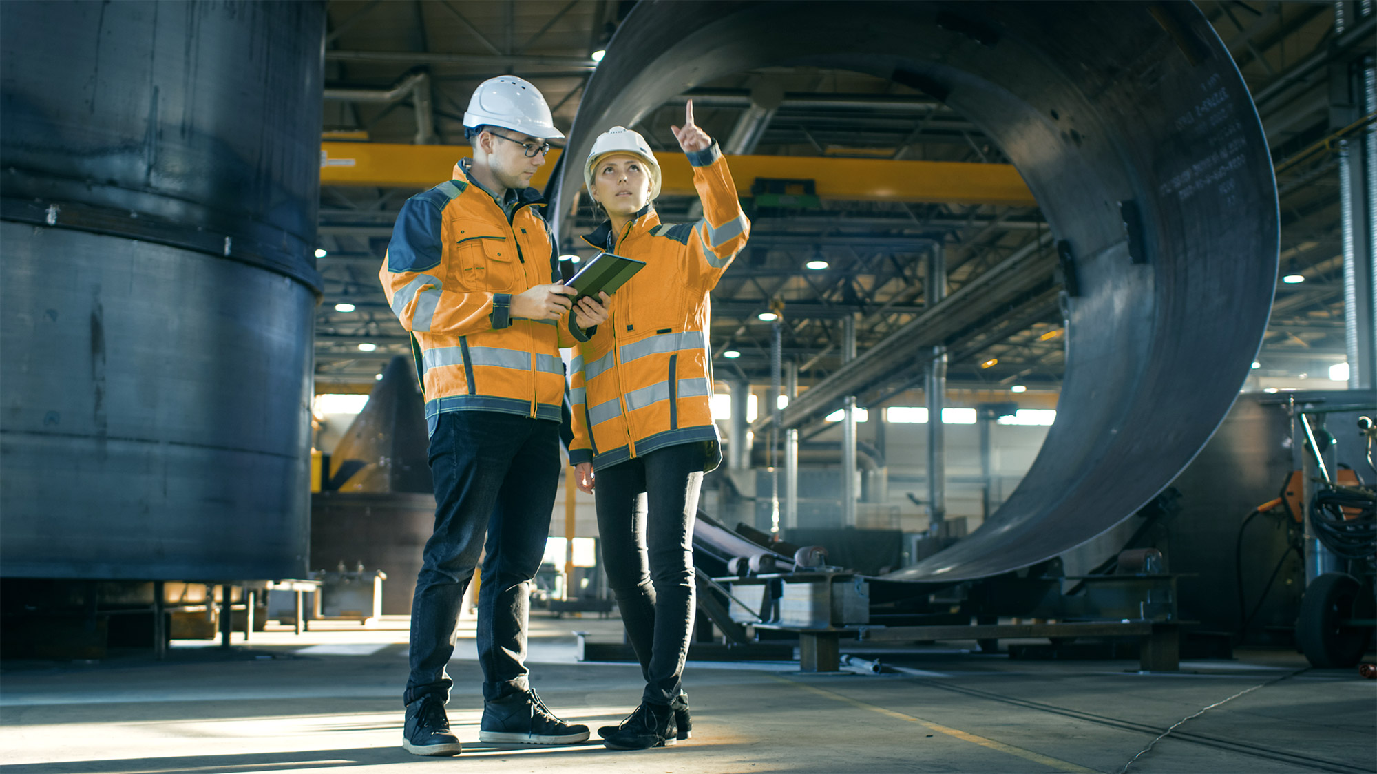 Man and woman looking at tablet in a place of production